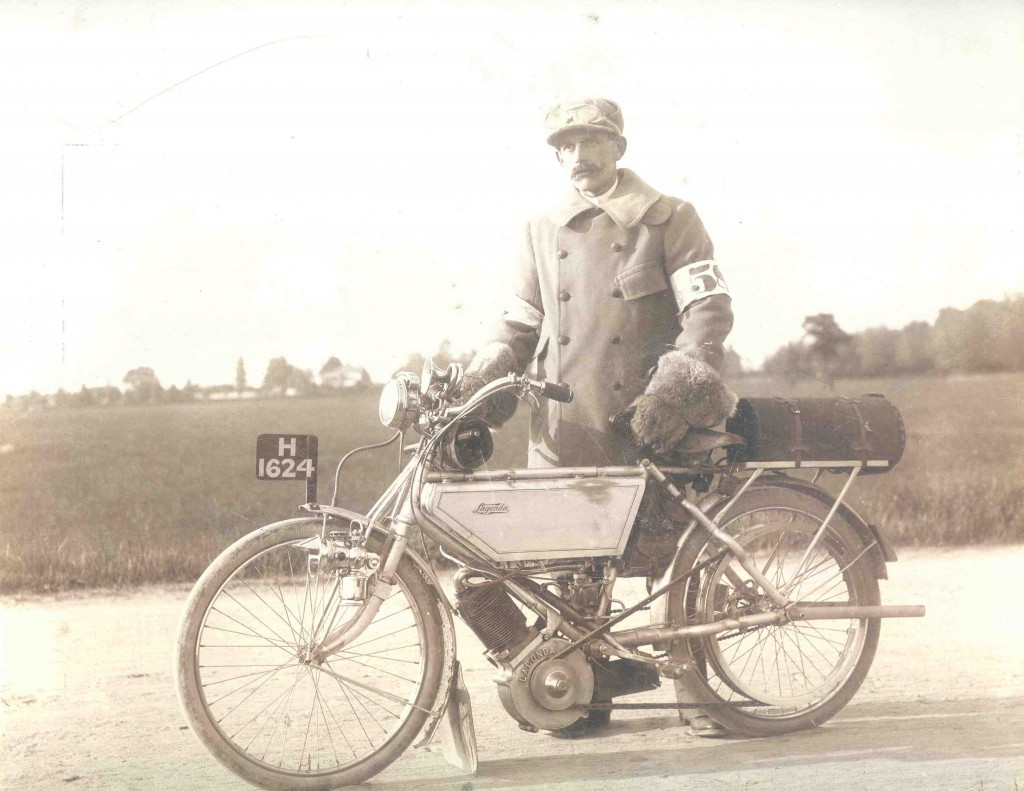 Lagonda motor cycle with a man wearing goggles, large fur gauntlets and armbands (numbered 58) circa 1904